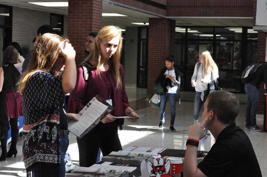 Anna Jackson and Madison Shrock walk around the college fair in the commons talking to sponsors of certain colleges, including Texas Tech.