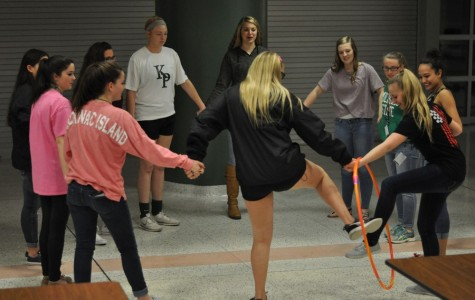Students at the NHS Conference play games such as holding hands and passing a hula hoop around and stepping through it to demonstrate teamwork.
