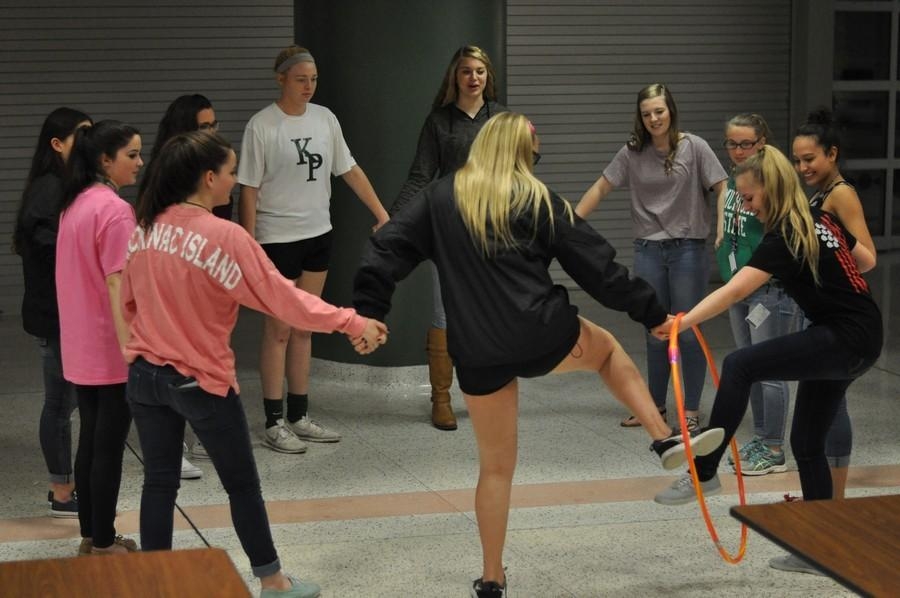 Students+at+the+NHS+Conference+play+games+such+as+holding+hands+and+passing+a+hula+hoop+around+and+stepping+through+it+to+demonstrate+teamwork.