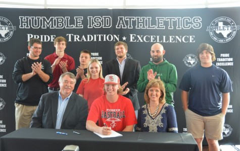 Curtis Rhodes signs to his college with friends and family standing with him in front of a crowd at Humble Civic Center.