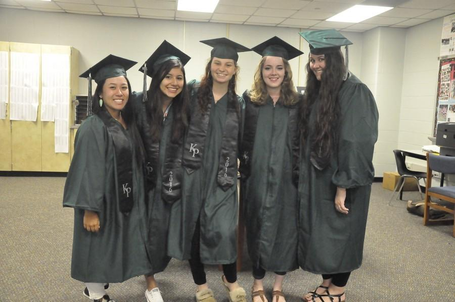 Senior journalism students try on cap and gowns.