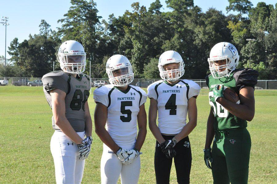 Luke Smith, Chris Luck, Matthew Wilding and CJ Awe pose on Kingwood Park's practice field to show off new helmets as well as possible uniform combinations.
