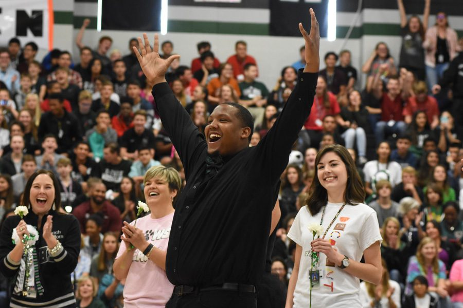 Criminal justice teacher Jerry Pollard throws up his hands and cheers at the October 28 Homecoming pep rally, after the announcement that he had become the staff  Homecoming king.
