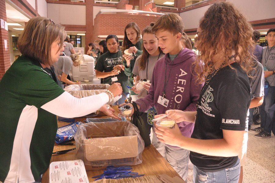 Students add topping to their free Culver's ice cream they received at lunch if they made all As or Bs on October 28.