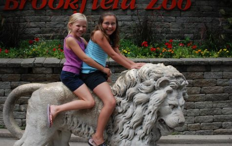 A young Sydney Woodward and McKenzie Dickerson pose sitting on one of the lions of Chicago's Brookfield Zoo.
