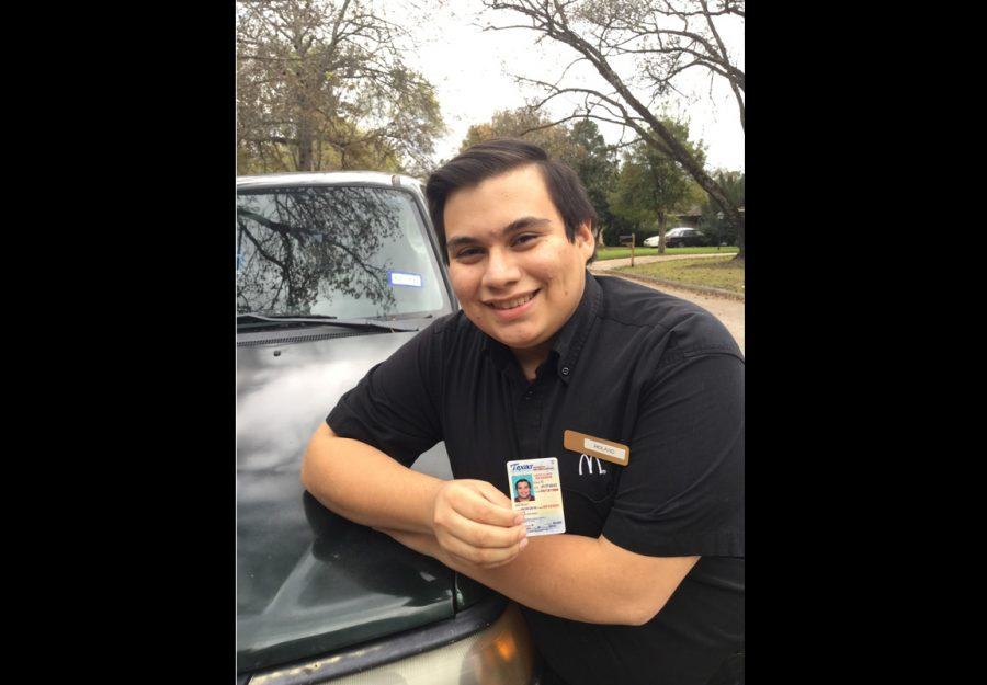 Senior Roland Garcia poses against his car with his drivers license.