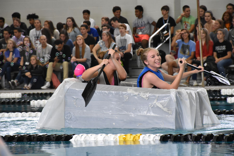 Juniors Jenny Leith and Emily Wilburn race their boat in the cardboard boat race during second period on May 18.