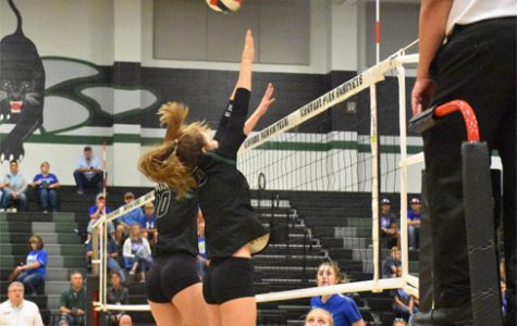 Varsity volleyball players senior Alex Plummer and junior Andie Unwin attempt to block a ball coming over the net in the Sept. 26 game against Barbers Hill.