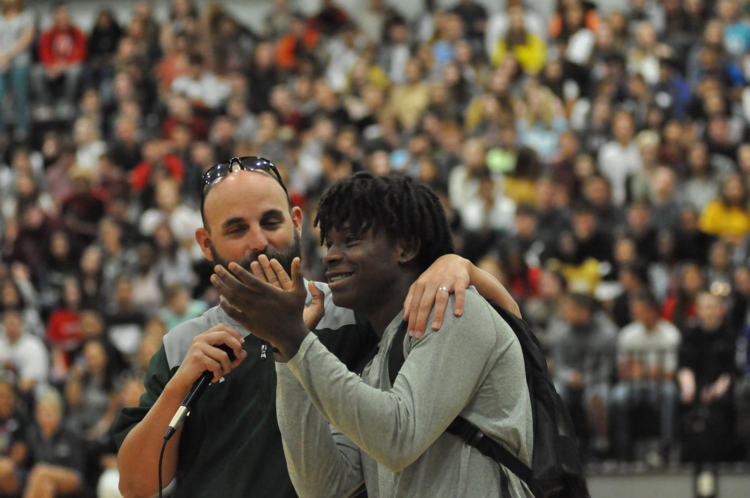 Offensive coordinator Bruce Cox introduces senior Tylan Johnson at the first pep rally as they encourage fans to show up for the football games this season.