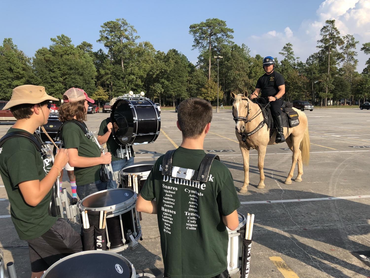 Members of the drumline visit with a Houston police officer as they prepare to play in front of the horses. The HPD brought their horses to the school to listen to the drumline to help prepare the horses to deal with the sounds of gunshots.