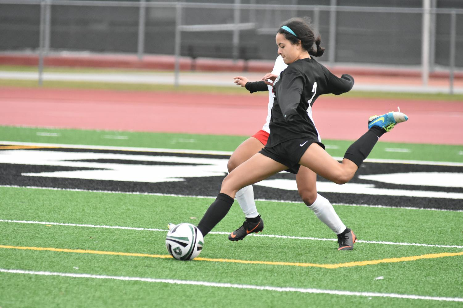 Senior Bella Salazar crosses the ball during an early season game at Kingwood Park.