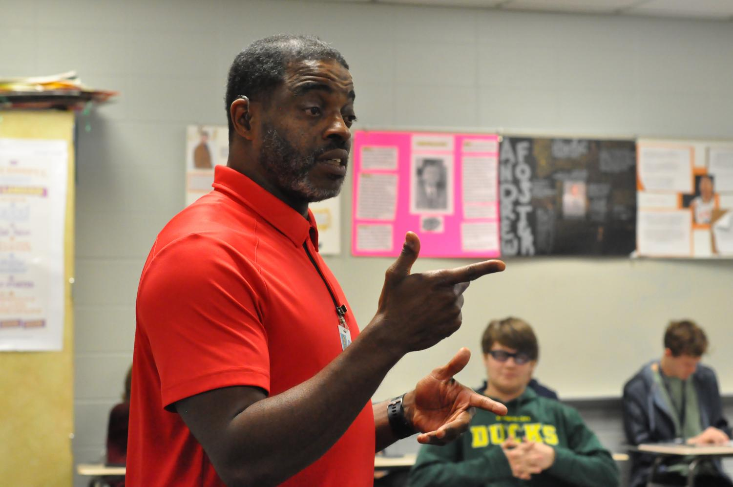 American Sign Language teacher Darnell Woods communicates with students in his fifth period class on March 22. Woods' mom first noticed he was hard of hearing when he was 5 years old. He has worn hearing aids since third grade, but his hearing has progressively worsened over time.