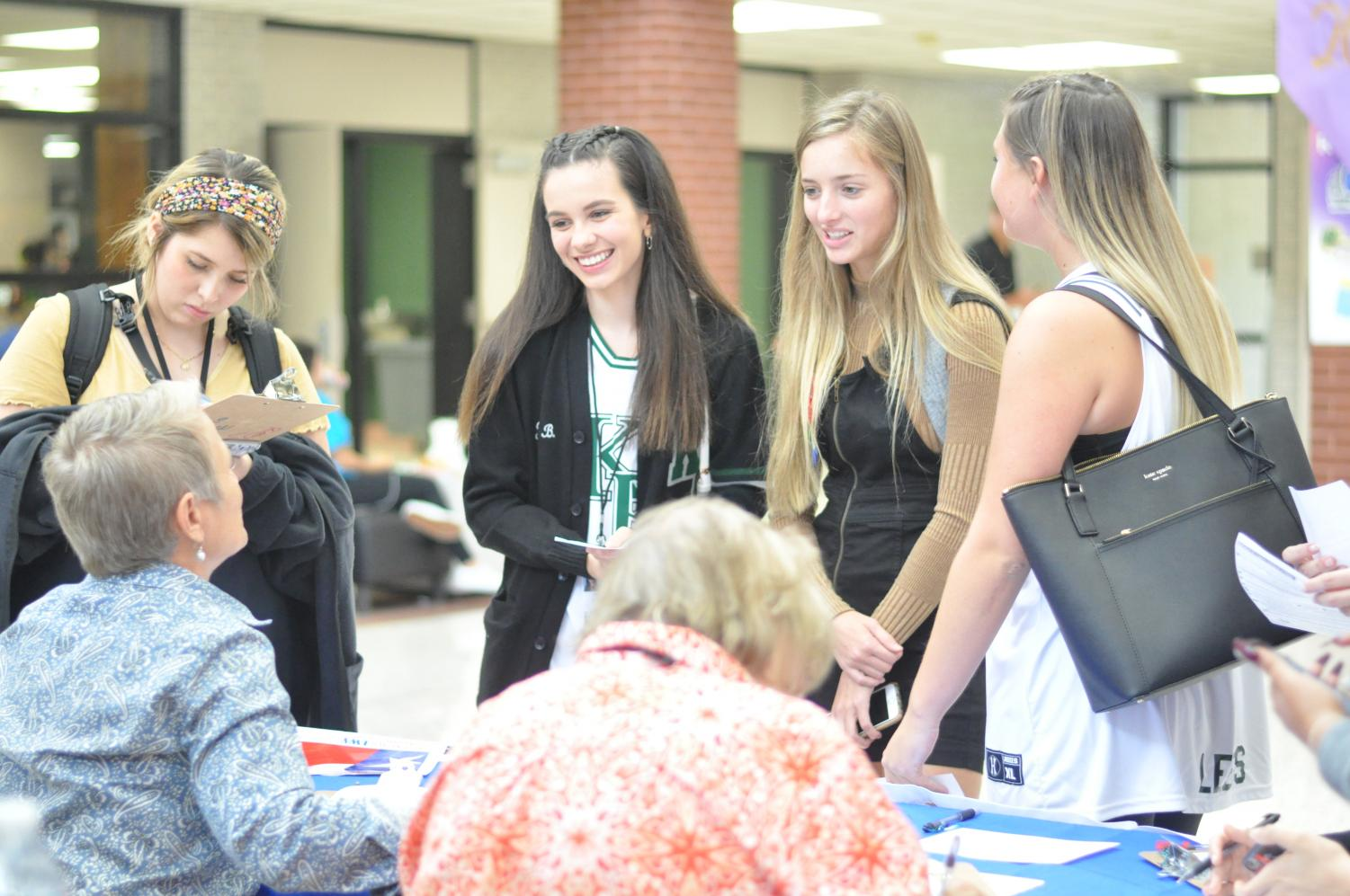 Seniors Giselle Roman, Jaclyn Brumfield, Hailey Dwight and Tanna Leeds talk with two women from the League of Women Voters who came during flex hour to register students to vote.