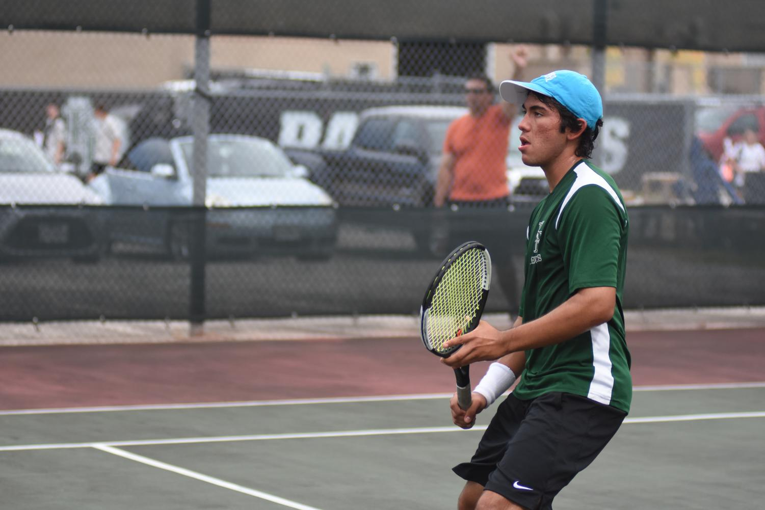 Robert Cornejo focuses during varsity tennis practice. He is one of two senior boys on the team and has been asked to teach tennis lessons.
