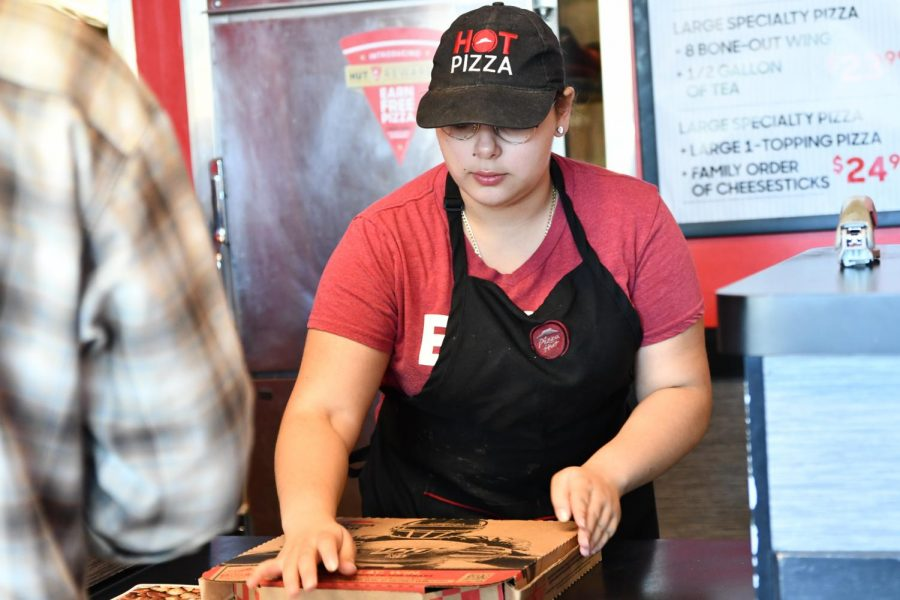 "Senior Jasmine Gaytan works the cash register at Pizza Hut on Kingwood Drive on Oct. 18. Gaytan has previously worked an office job at a construction company called Pipeline, the restaurant The Donkey and Starbucks. ""[High school students] do need a job because that's the way of life now,"" Gaytan said. ""Everybody needs money, money's everything."""