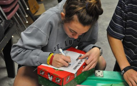 Junior Trezzie Ivy writes a Christmas letter to add into her shoe box.