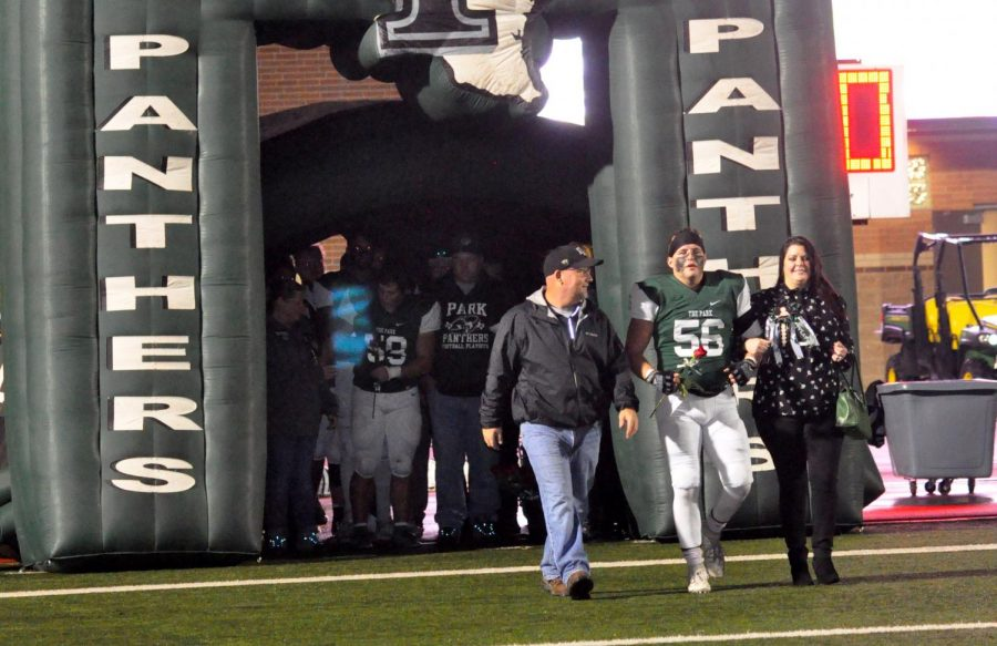 Luke Pavlat walks onto the field with his mom and dad on senior night.