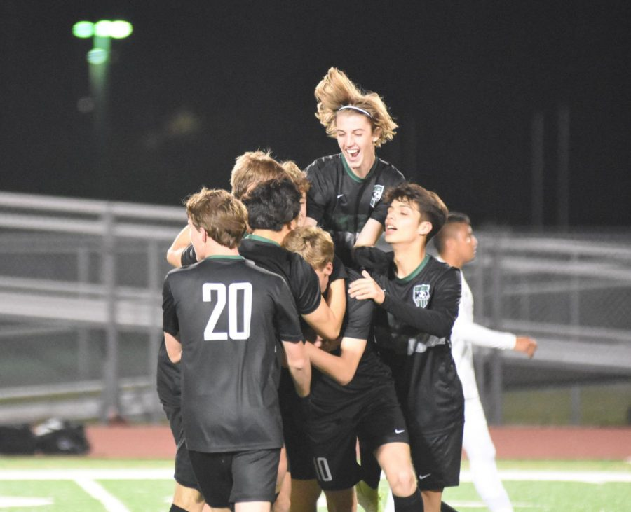 Senior Jake Bruce jumps in the air as his teammates celebrate a goal in a huddle around him. The team won the game against Sharpstown, the team that beat them in the Regional Finals last year.