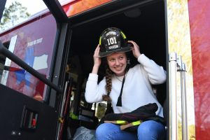 "Sophomore Kate Tiedtke sits in a Houston Fire Station 101 fire truck on Feb. 21. After going into cardiac arrest Kate visited the firefighters often to sit and talk with them. ""The experience to thank the firefighters was one of a kind,"" Kate said. ""They never get the appreciation they deserve. During their job they see the worst things in life like people's death and their suffering. It is very hard for them to be happy sometimes because of this. At the reunion, they all looked so happy, and that is all I would ever want for them, because they're like friends to me."""