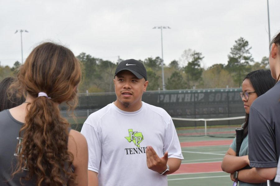 Tennis coach John Macapaz works with some of his players during a practice in March at the tennis courts.