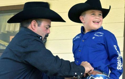 Jeff Wilson adjusts the gear his son Shiloh, 7, wears each time he competes in saddle bronc riding at rodeos. His father, who teaches collision and refinishing, retired from rodeo in 2004. He was a saddle bronc champion in 2002.