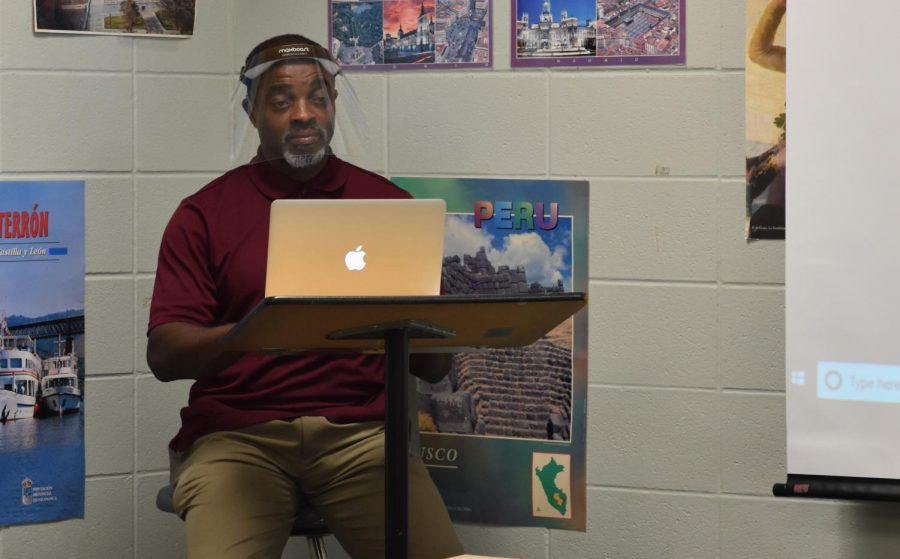 American+sign+language+teacher+Darnell+Woods+teaches+from+his+podium+in+the+corner+of+his+room+during+a+September+class.+Since+lip+reading+is+a+key+part+of+ASL%2C+Woods+started+the+year+wearing+a+face+mask.+He+eventually+switched+to+a+see-through+mask+that+covers+his+nose+and+mouth+when+he+was+able+to+secure+one.+