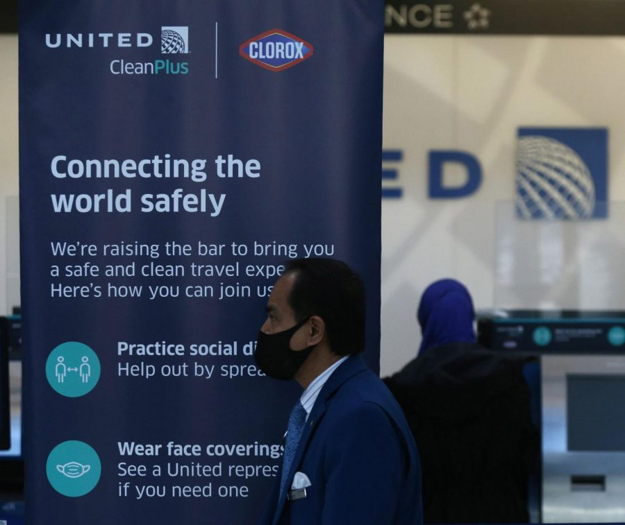 A sign informs travelers on COVID-19 guidelines at the United Airlines check-in area in Terminal 1 at O'Hare International Airport in Chicago on Nov. 12.
