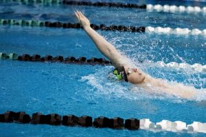 Senior Logan Rushing competes in the 100 backstroke on Jan. 8 in the final home meet of the season.