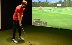 Sophomore Jayden Romig lines up his shot in the golf room, where the students are able to practice with the new TrackMan. The new technology allows the players to practice in competition-like situations, even when being on a course is not possible.