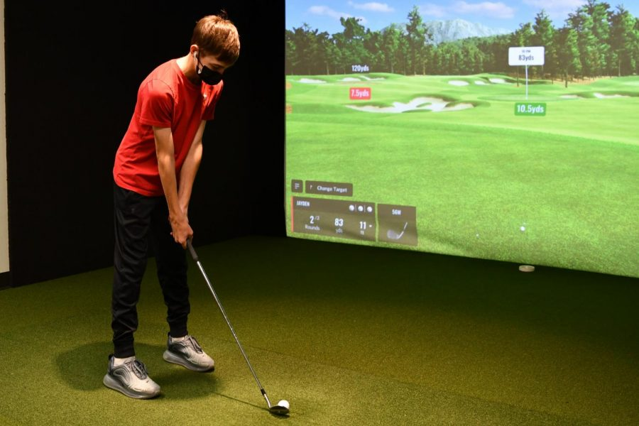 Sophomore+Jayden+Romig+lines+up+his+shot+in+the+golf+room%2C+where+the+students+are+able+to+practice+with+the+new+TrackMan.+The+new+technology+allows+the+players+to+practice+in+competition-like+situations%2C+even+when+being+on+a+course+is+not+possible.