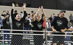 Parents cheer at the railing as they celebrate the boys soccer team's 5-4 victory over Pharr Valley View in the state semifinals. Despite games being so far away, the families and Kingwood Park community have traveled to watch the team play.