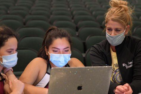 Silver Stars Daniella Lugo Castro and Danae Montes work with dance teacher Cyndi Vaughn to cut music during class.