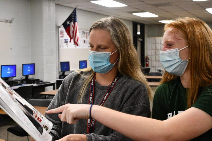 Journalism teacher Megan Ortiz looks over a yearbook spread with freshman Arleigh Doehring.