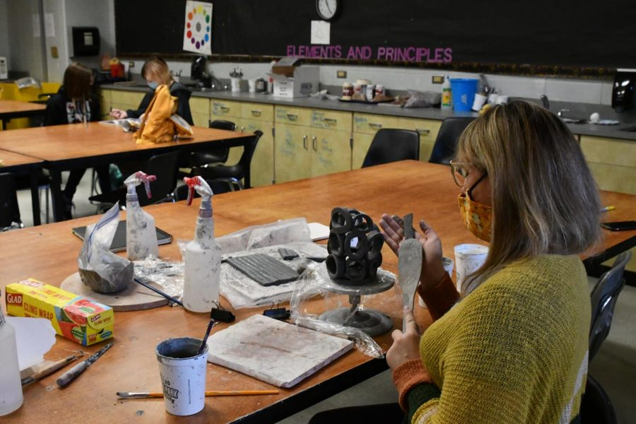 Lara Webb works on a vase alongside her students in fifth period on May 7.