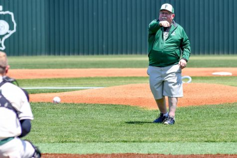 Joe Ehrhardt throws out the first pitch at the varsity baseball game against Dayton on April 24. Ehrhardt teaches Principles of Physics and Astronomy. He has always been a major supporter of the baseball team.
