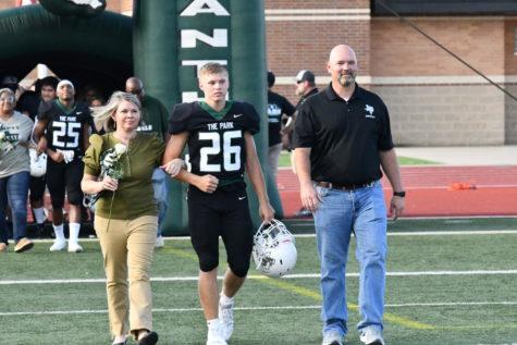 Senior Cameron Fain walks out with his family on senior night.