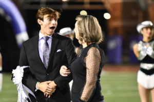 Senior Kade Terrell looks at his mom in shock as he hears his name announced as the homecoming king during halftime of the football game on Oct. 15.