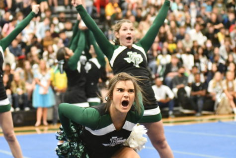 Molly Scott, 12, performs with the other cheerleaders as they kick off the pep rally with a routine to fire up the students at the homecoming pep rally on Oct. 15.