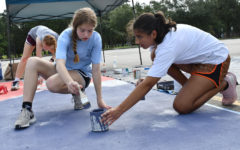 With help from juniors Emma Yeager and Katie Gerbasich, senior Kathleen Ortiz paints her parking spot on Sept. 4.